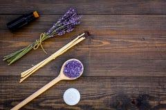 护肤和放松 化妆用品和芳香疗法概念 淡紫色温泉盐和油在黑暗的木背景顶视图 库存图片