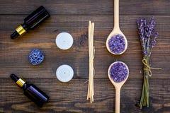 护肤和放松 化妆用品和芳香疗法概念 淡紫色温泉盐和油在黑暗的木背景顶视图 库存照片