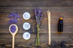 护肤和放松 化妆用品和芳香疗法概念 淡紫色温泉盐和油在黑暗的木背景顶视图 免版税库存照片