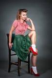 画报女孩坐在灰色背景的一把椅子在一条红色女衬衫和绿色裙子穿戴了在脚白色袜子和红色鞋子 库存图片