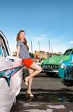 画报的女孩在减速火箭的汽车背景  免版税库存照片