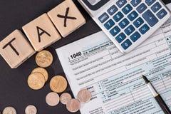 1040报税表和木立方体,计算器 库存照片