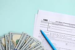 1065报税表在一百元钞票和蓝色笔附近说谎在浅兰的背景 parentship收入的美国回归 免版税库存图片