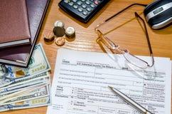 1040报税表在2016年与笔,玻璃,美元 免版税库存图片