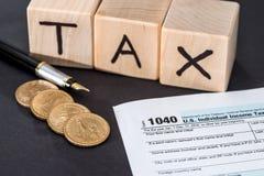 1040报税表,木立方体收税笔和硬币 免版税库存图片