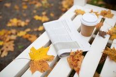 报纸和咖啡杯在长凳在秋天停放 库存图片