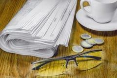 报纸咖啡和玻璃在桌上 免版税库存照片