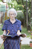 读报纸的九十个岁夫人在后院 库存图片
