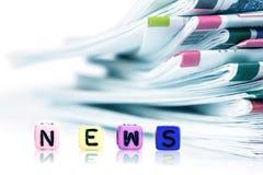 报纸的堆与新闻五颜六色的词立方体的  免版税图库摄影