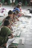 读报纸的孩子在一则全国新闻 库存照片