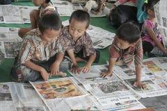 读报纸的孩子在一则全国新闻 免版税库存图片