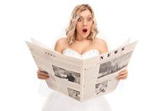 读报纸的惊奇的年轻新娘 免版税图库摄影