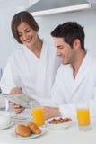 读报纸的愉快的人,当食用早餐时 免版税库存图片