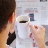 读报纸的成年男性饮用的咖啡 免版税库存图片