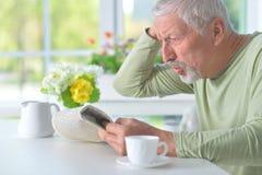 读报纸的美丽的老人 免版税图库摄影
