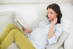 读报纸的被集中的怀孕的棕色毛发的妇女 免版税库存图片