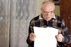 读报纸的高兴老人 免版税库存照片