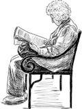 读报纸的年长妇女 库存照片