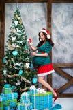画报衣服的怀孕的女孩在圣诞树附近 图库摄影
