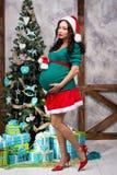 画报衣服的怀孕的女孩在圣诞树附近 库存照片