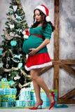 画报衣服的怀孕的女孩在圣诞树附近 免版税库存照片