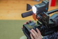 报道事件用一台摄象机 Videographer采取有赠送阅本空间的摄像头文本的 摄像头操作员 图库摄影