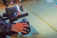 报道事件用一台摄象机 Videographer采取有赠送阅本空间的摄像头文本的 摄像头操作员 免版税库存图片