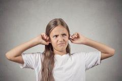 报道她的耳朵喧闹声的懊恼女孩在楼上 免版税库存照片