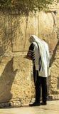 披巾的祈祷在哭墙一个重要犹太宗教站点的未认出的犹太崇拜者和tefillin 免版税库存照片