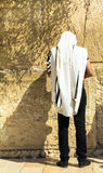 披巾的祈祷在哭墙一个重要犹太宗教站点的未认出的犹太崇拜者和tefillin 免版税图库摄影