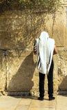 披巾的祈祷在哭墙一个重要犹太宗教站点的未认出的犹太崇拜者和tefillin 免版税库存图片