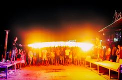 披披岛,泰国, 2017年11月13日:跳火焰状绳索的快活的青年人 集会在发埃发埃的人群 库存图片