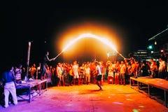 披披岛,泰国, 2017年11月13日:跳火焰状绳索的快活的青年人 集会在发埃发埃的人群 免版税库存图片