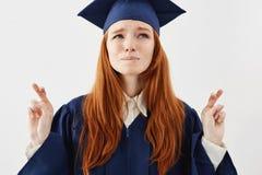 披风的祈祷对成功的美丽,并且紧张的红头发人毕业生女孩画象作为未来律师或医生手指 免版税库存照片