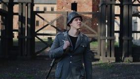 抬他的头的一名年轻英俊的德国士兵的画象 在背景的集中营重建 股票视频