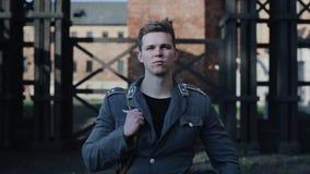 抬他的头的一名年轻英俊的德国士兵的画象 在背景的集中营重建 股票录像