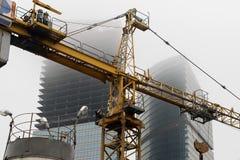 抬头在建设中摩天大楼背景一场雾的在一个被放弃的建造场所 库存图片