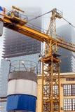 抬头在建设中摩天大楼背景一场雾的在一个被放弃的建造场所 免版税图库摄影
