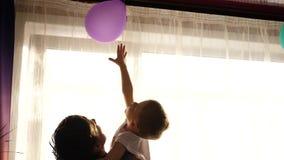 抱他的小孩子的年轻父亲在窗口附近 太阳光芒通过窗口 孩子的笑声和喜悦 股票录像