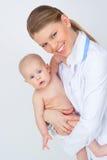 抱可爱的孩子的愉快的微笑的儿科医生治疗师妇女 免版税库存照片