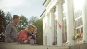 抱和拥抱他们可爱的孩子的年轻父母 美好的光 股票视频
