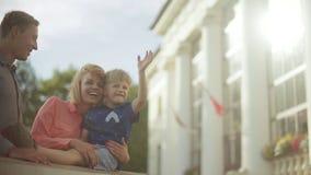 抱和拥抱他们可爱的孩子的年轻父母 美好的光 股票录像