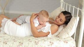 抱她的婴儿的年轻母亲 使用与她新出生的儿子的年轻妈妈 股票录像