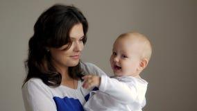 抱她的婴儿的年轻愉快的母亲 房子图象JPG向量 美丽的微笑的妈妈和婴孩一起 免版税库存图片