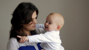 抱她的婴儿的年轻愉快的母亲 房子图象JPG向量 美丽的微笑的妈妈和婴孩一起 图库摄影