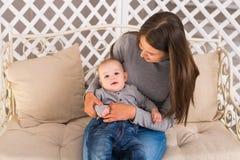 抱她的婴儿的年轻母亲 妈妈护理婴孩 妇女和新出生的男孩在屋子里 使用与的母亲 库存图片