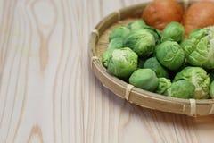 抱子甘蓝和红萝卜在竹滤锅 库存图片