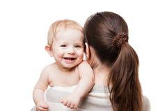 抱小新出生的微笑的小孩子的爱恋的母亲 免版税库存照片