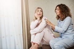 抱怨和抱怨她的男朋友的生气阴沉的女朋友 有卷发的可爱的女孩在睡衣 库存照片