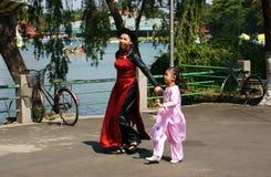 抱手孩子的母亲走在公园 免版税图库摄影